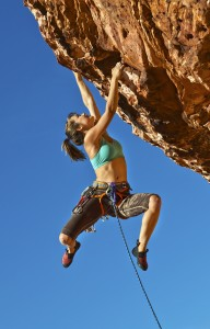 Female climber clinging to the edge.
